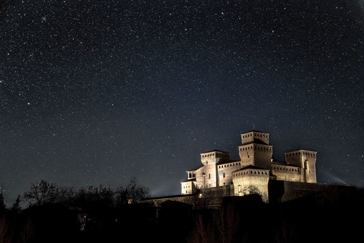Low angle view of illuminated castle against sky at night, torrechiara parma italy