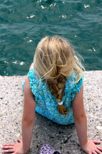 Rear view of girl sitting on pier against lake