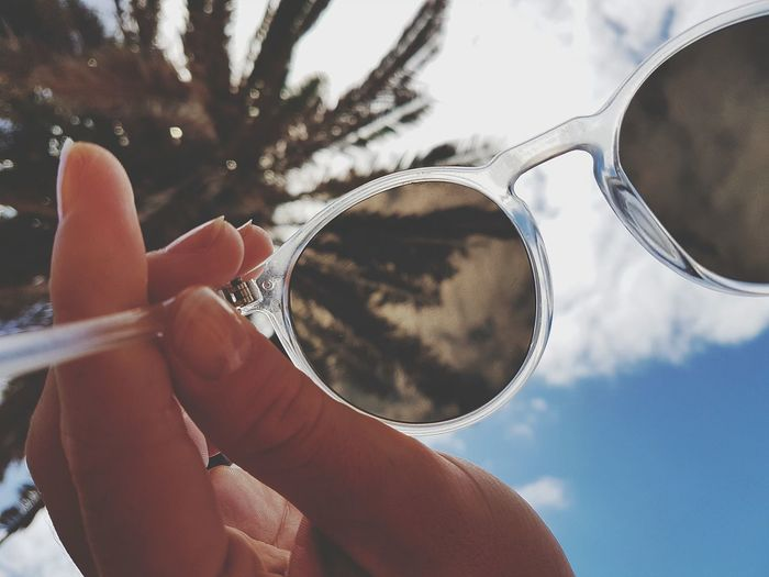 Cropped Hand Of Woman Holding Sunglasses Against Sky