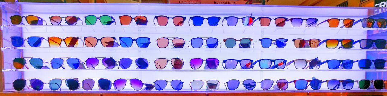 Full Frame Shot Of Colorful Sunglasses On Shelves In Store For Sale