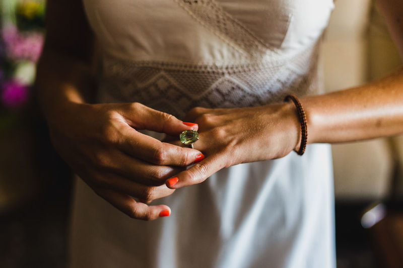 Midsection of bride wearing ring standing at home