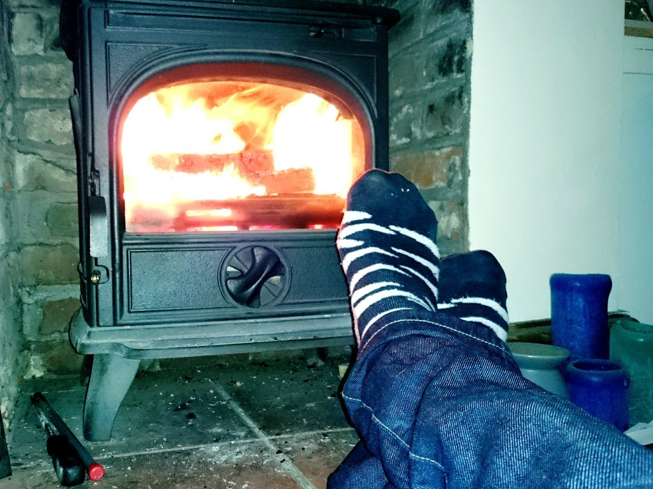 low section, human leg, personal perspective, heat - temperature, real people, one person, indoors, human body part, men, flame, burning, shoe, fireplace, day, close-up, human hand, people