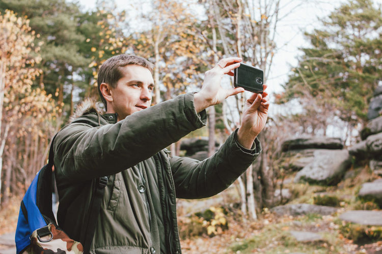 Man photographing by mobile phone while standing in forest