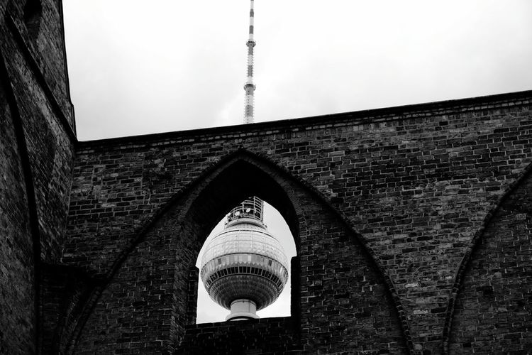 Low Angle View Of Television Tower - Berlin Seen Through Brick Wall