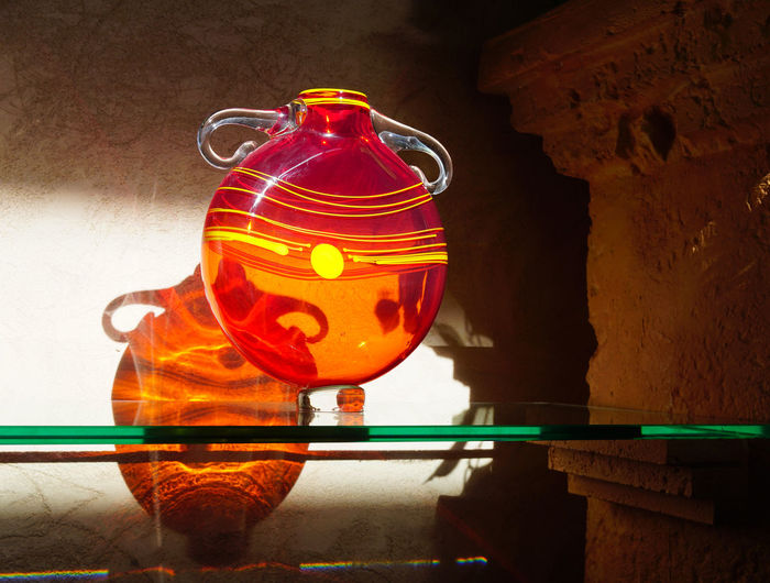 Close-up of illuminated lantern on table against wall