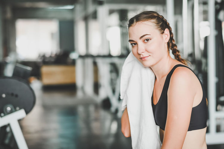 Portrait of smiling young woman wiping face while exercising in gym