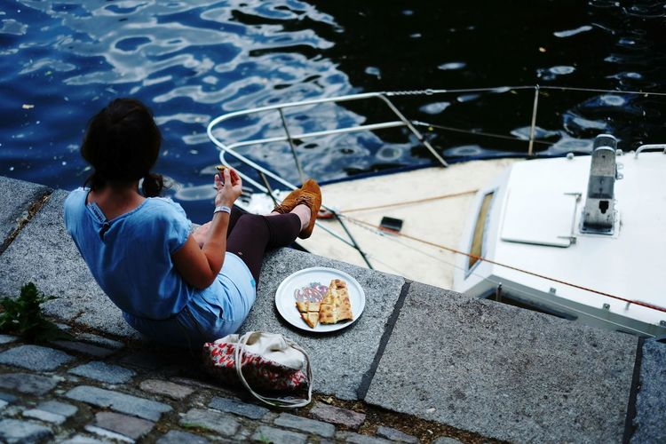 Woman Eating On Waterfront