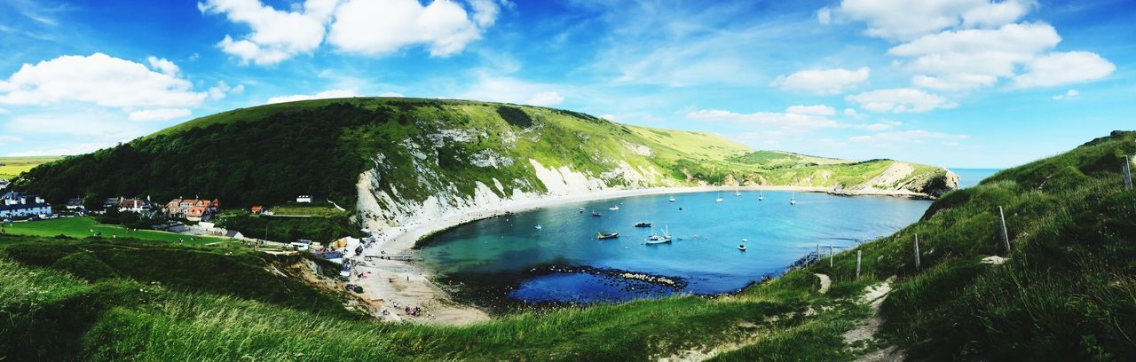 Panoramic view of lulworth cove by mountains against sky