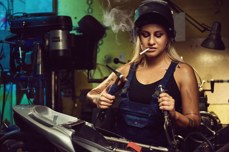 Woman mechanic working in a motorcycle workshop Mechanic Motorcycle Smoke Smoking Transport Transportation Welding Woman Work Worker Working Workplace Workshop Bike Biker Blond Female Garage Indoors  Job Moto Repair Welding Work Young Adult Young Women