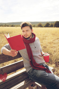 One Person Sitting Holding Young Adult Relaxation Red Leisure Activity Adult Casual Clothing Land Field Nature Food And Drink Drink Day Cup Looking At Camera Portrait Outdoors Drinking Reading Read Reading A Book Book