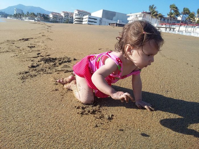 Cute girl playing on sand at beach