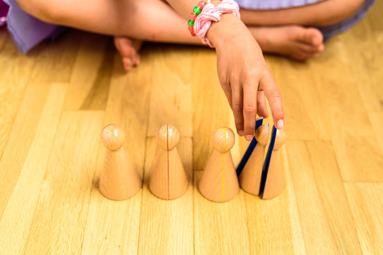 Low section of girl playing with tokens while sitting on hardwood floor