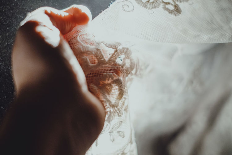 Close-up of woman hand on bed