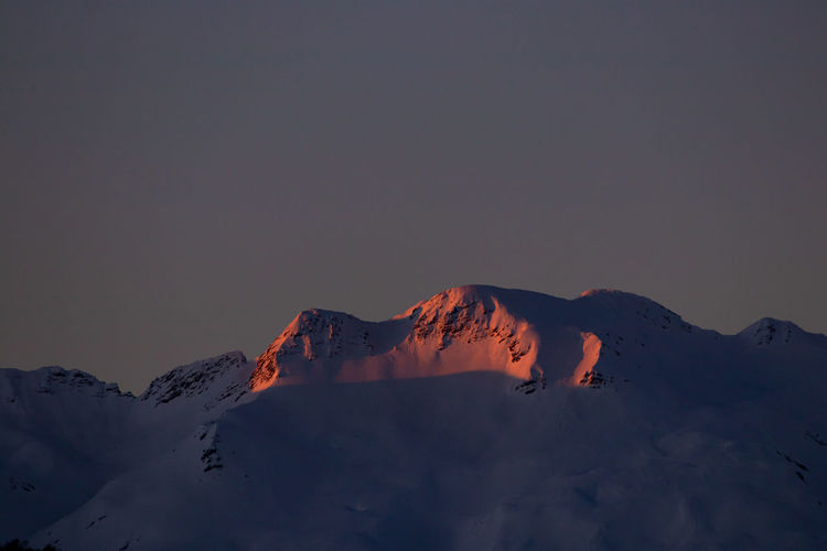 Scenic view of snow covered mountain against sky during sunset