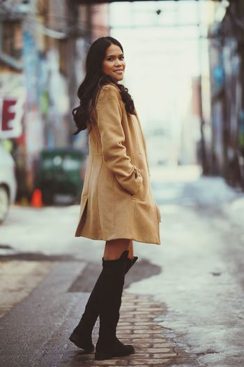 Young woman standing on footpath in city