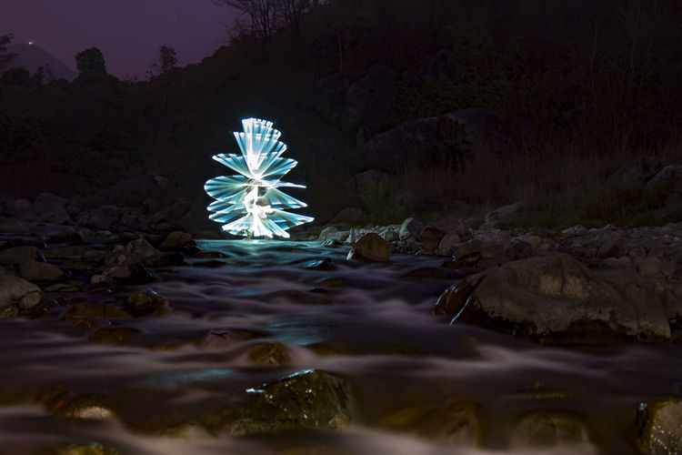 Illuminated light painting on rock by river at night