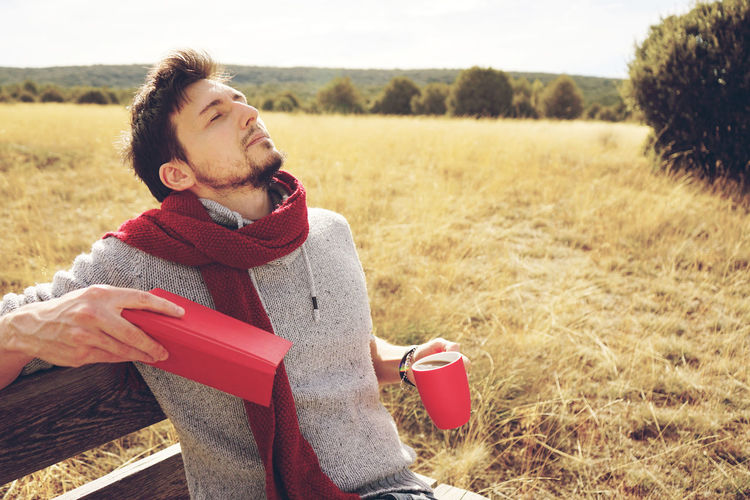 One Person Young Adult Casual Clothing Field Nature Leisure Activity Relaxation Land Day Sitting Landscape Holding Lifestyles Real People Red Clothing Rural Scene Adult Grass Outdoors Scarf