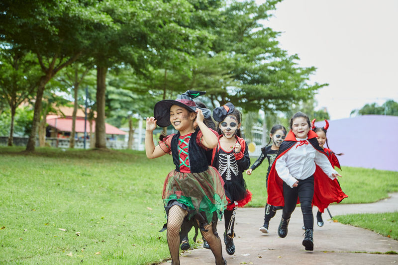 Girls in costumes running on footpath during halloween