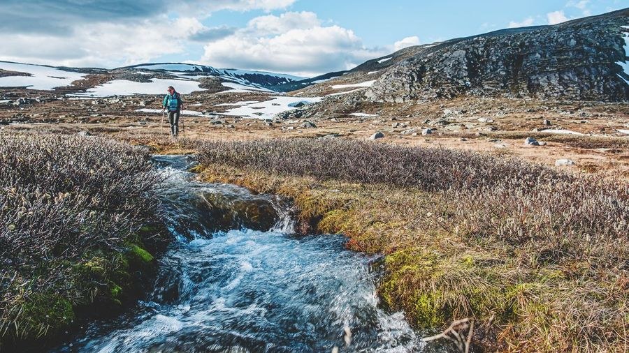 Woman walking by stream on land during winter