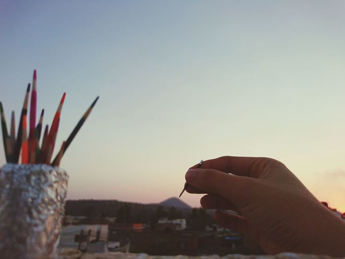 Close-up of hand painting against clear sky
