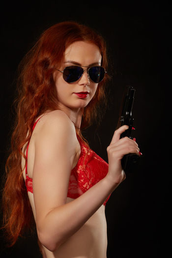 Portrait of young woman holding sunglasses against black background