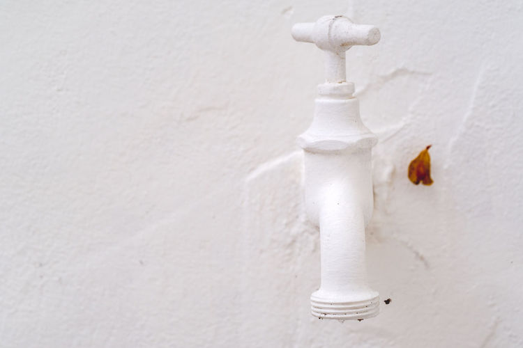 Close-up of white faucet against wall
