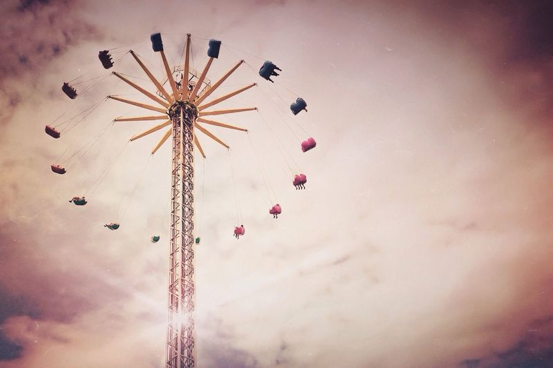Low angle view of swing ride against clouds