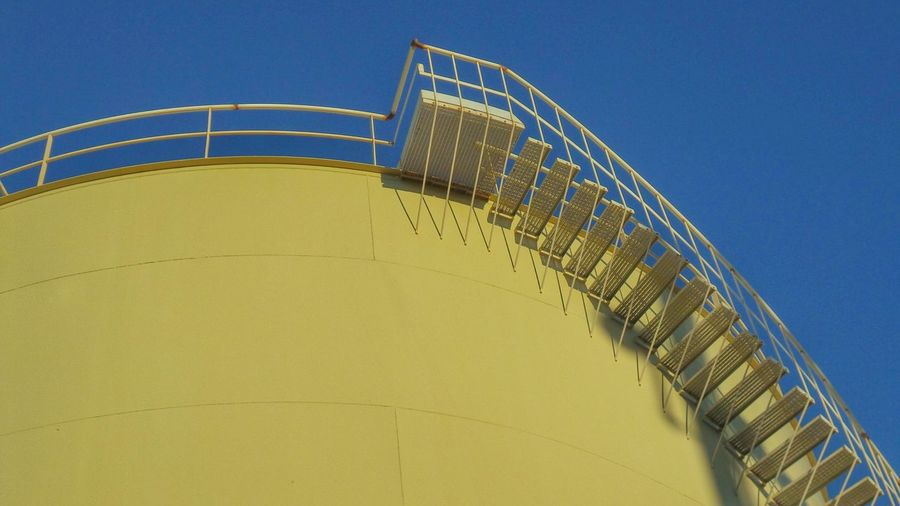 Low Angle View Of Yellow Oil Storage Tank Against Clear Blue Sky