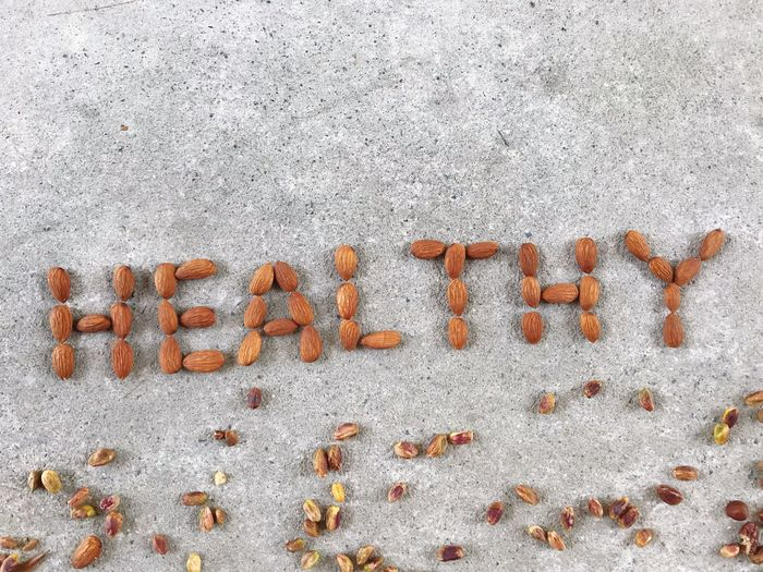 Top view of word HEALTHY from almond nuts with pistachios on concrete foor Healthy Food Concept Variety Of Nuts Roasted Almonds Mock Up Word Concrete Almond Pistachio Healthy Food Healthy Eating Top View Healthy Concept Letter Alphabet Letters EyeEm Selects Text Western Script Communication Capital Letter No People White Color Day Textured  Sign Single Word Close-up Outdoors High Angle View Creativity Pattern