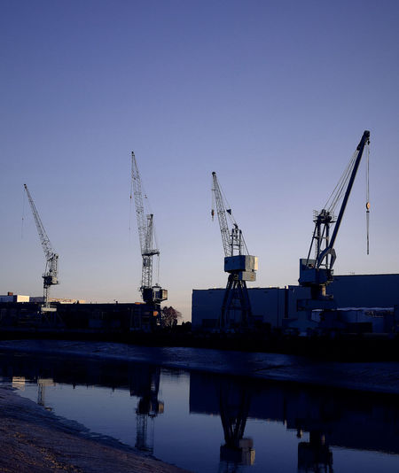 Cranes at harbor against clear sky