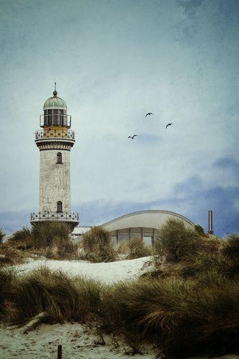 Warnemunde lighthouse at beach against sky