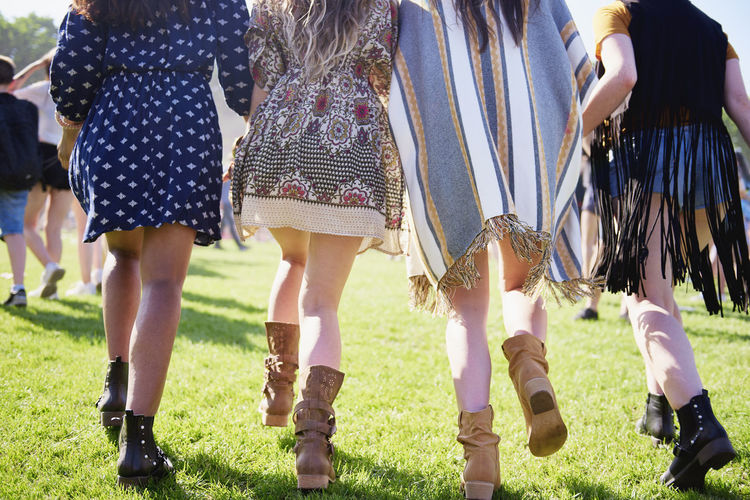 Low section of women walking on grass