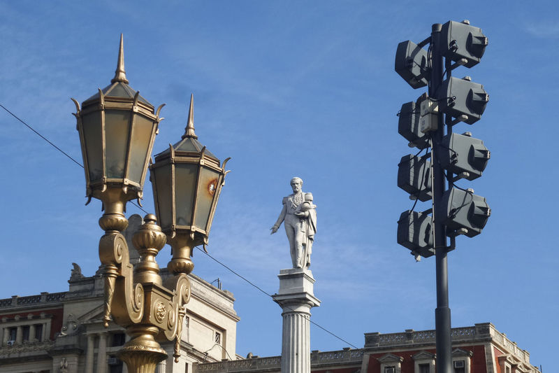 Low angle view of lighting equipment and general juan lavalle column at plaza lavalle against blue sky