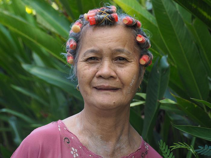 Portrait of senior woman against plants