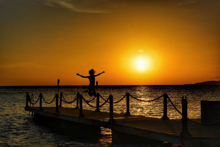 Silhouette girl jumping on pier over sea during sunset