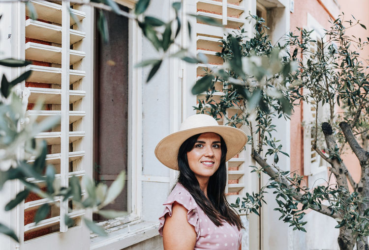 Portrait of a beautiful young woman, summer, olive tree, pastel colors, smile, lifestyle, fashion.