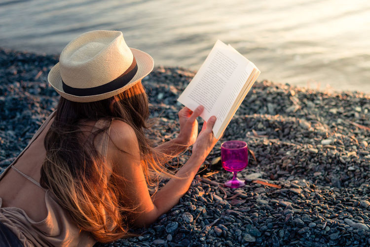 Enjoying sunset at the beach with a book and a glass of wine Beach Beauty Book Drink Hat Nature Pebble Beach Reading Sea Summer Sunset Vacations Woman Enjoy The New Normal Live For The Story Sommergefühle
