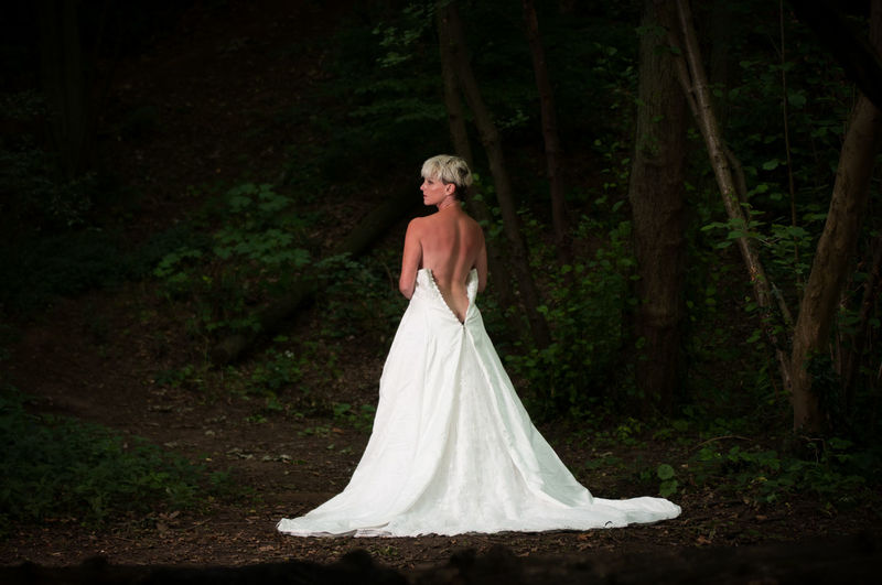 Rear view of bride wearing backless wedding dress in forest