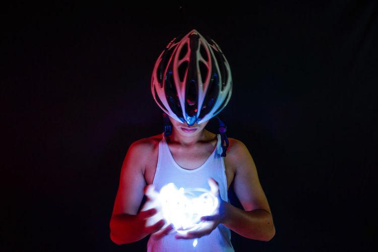Man holding illuminated string lights against black background