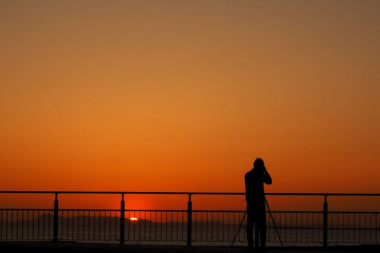 Silhouette man standing by railing towards sea against clear orange sky