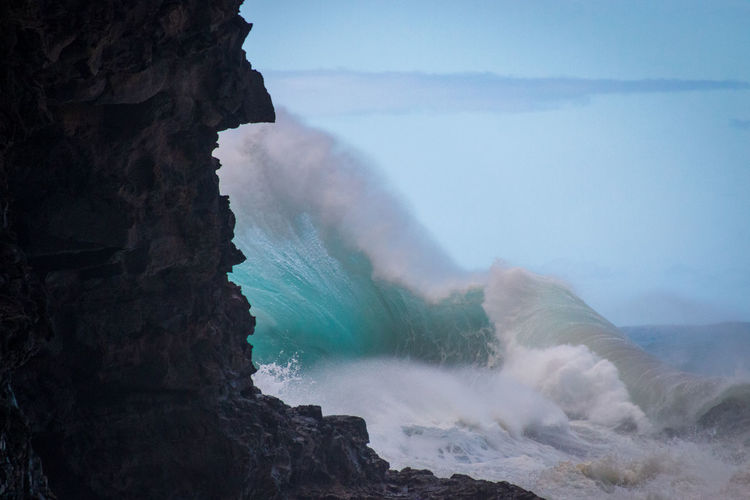 Spectaculat waves crashing at hanakapiai beach on the hawaiian island of kauai, usa against sky