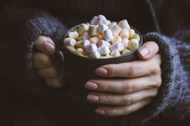 Midsection of woman carrying marshmallows in cup