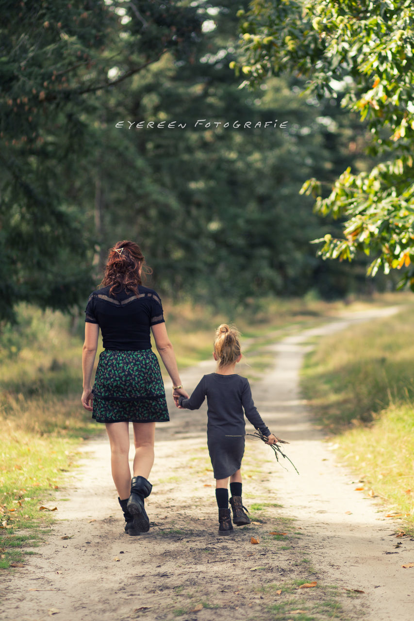 rear view, two people, women, walking, real people, adult, plant, full length, togetherness, lifestyles, casual clothing, tree, leisure activity, nature, people, the way forward, females, family, focus on foreground, day, hairstyle, outdoors, daughter