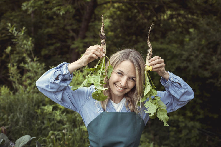 Portrait of a smiling young woman holding plants