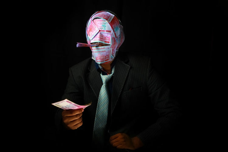 Portrait of young man holding paper against black background