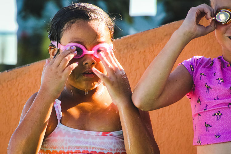girls, summertime poolside, putting on swimming goggles Real People Front View Lifestyles Leisure Activity Portrait Holding Focus On Foreground Headshot Waist Up Day Females Poolside Girls Swimming Goggles Eyewear Summer Wet Diversity The Portraitist - 2019 EyeEm Awards