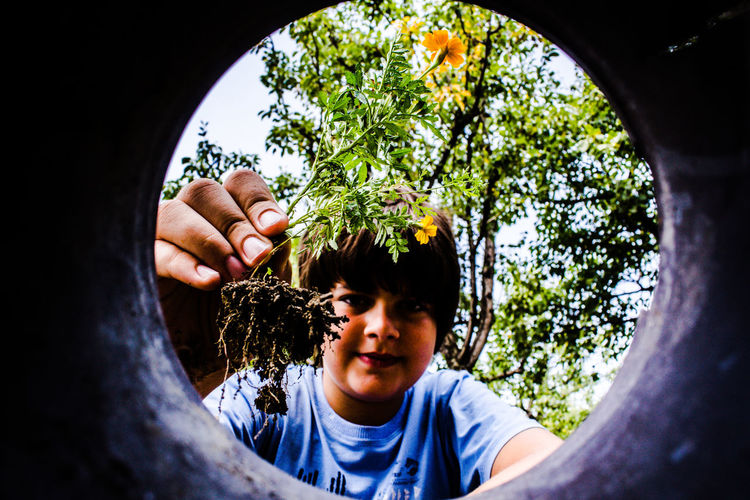 Low angle portrait of smiling boy holding flowering plant against trees