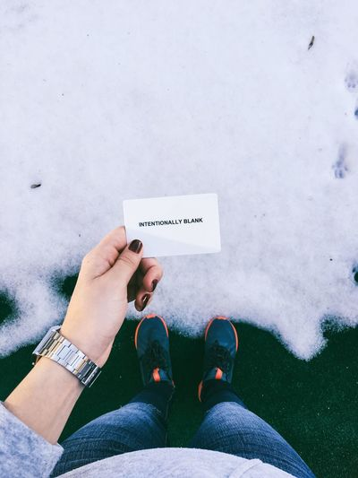 High angle view of woman holding card with text on snow covered field