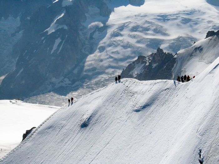 High angle view of tourists on snow covered mountain