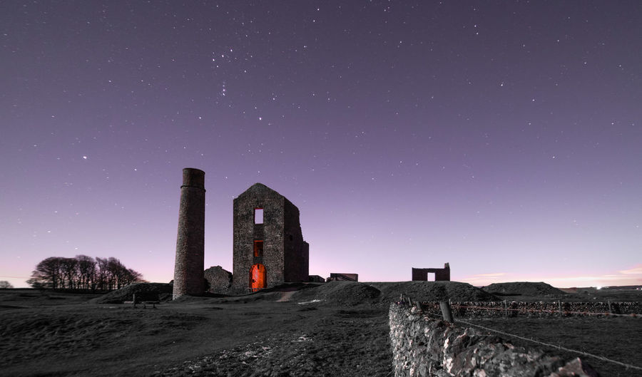 Low angle view of old ruin against clear sky at night